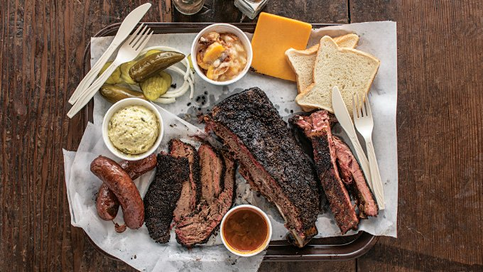 A tray of meat featuring the massive beef rib, as well as brisket, sausage, and pork ribs.