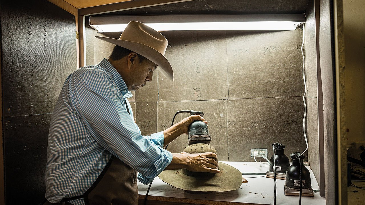 Funmaker sanding a hat to give it a more finished look.