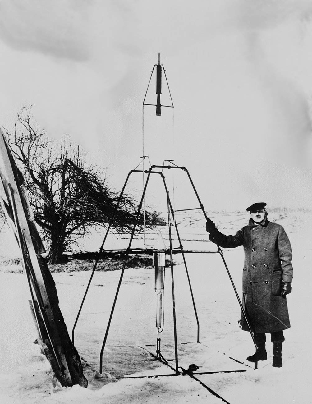 Dr. Robert H. Goddard and his liquid-fueled rocket in the frame from which it was fired on March 16, 1926, at Auburn, Mass.